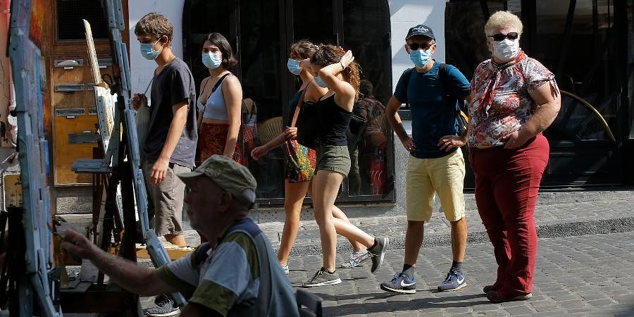 A fainter works while tourists stroll in the Montmartre district Monday, Aug. 10, 2020 in Paris.