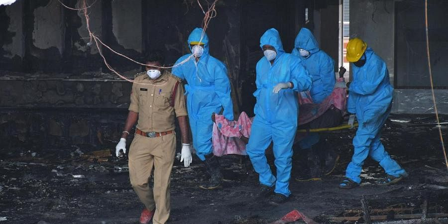 Fire fighters and medical staff transport bodies of deceased coronavirus patients to mortuary from Swarna Palace