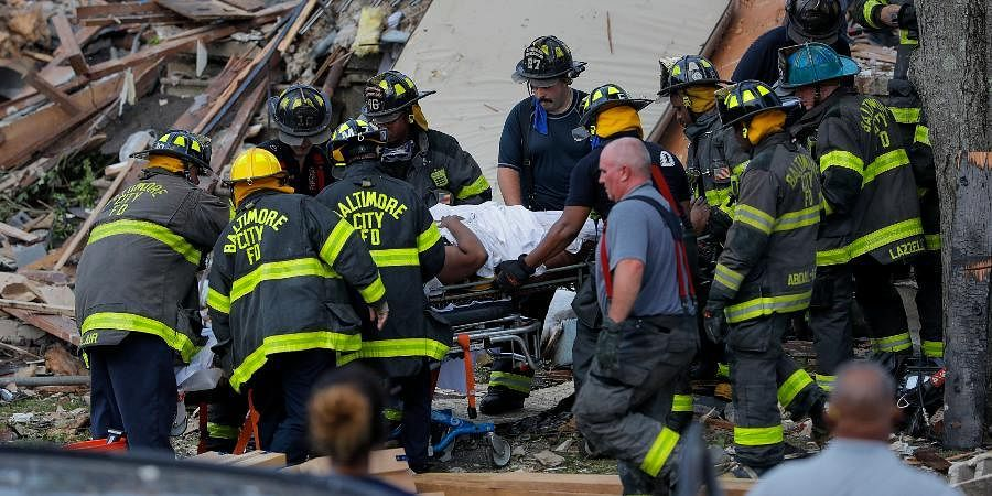 Baltimore City Fire Department carries a person out from the debris after an explosion in Baltimore on Monday.