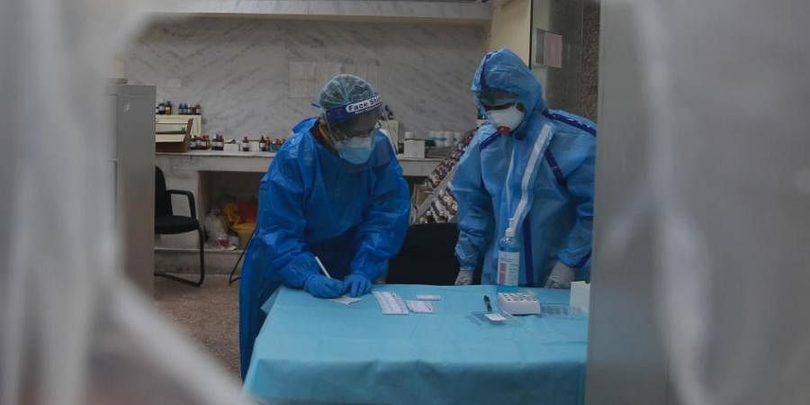 Health workers collect swab samples for coronavirus through rapid antigen tests in New Delhi.