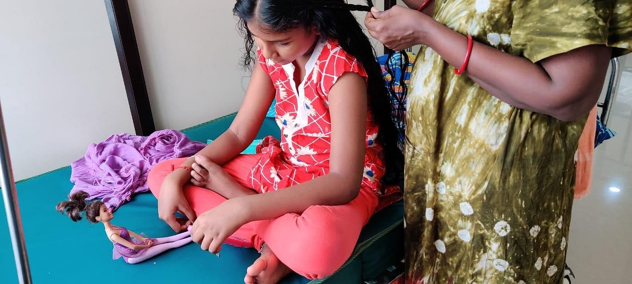Not So Alone - At 09:00 AM, Sometimes an entire family will be admitted, making the ward their new ward their new home. A girl is seen getting her hair tied by her mother. (Photo | EPS/Shiba Prasad Sahu)