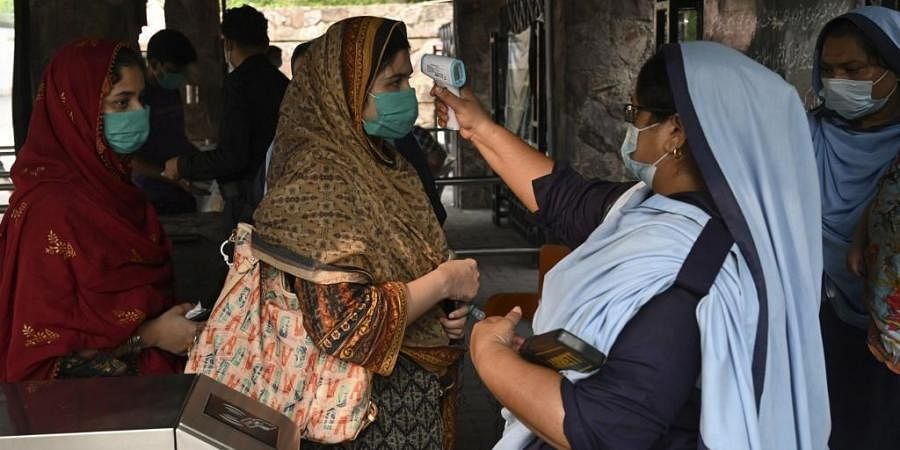 An official (R) checks the body temperature of a woman before entering at a Zoo in Lahore. (Photo | AFP)