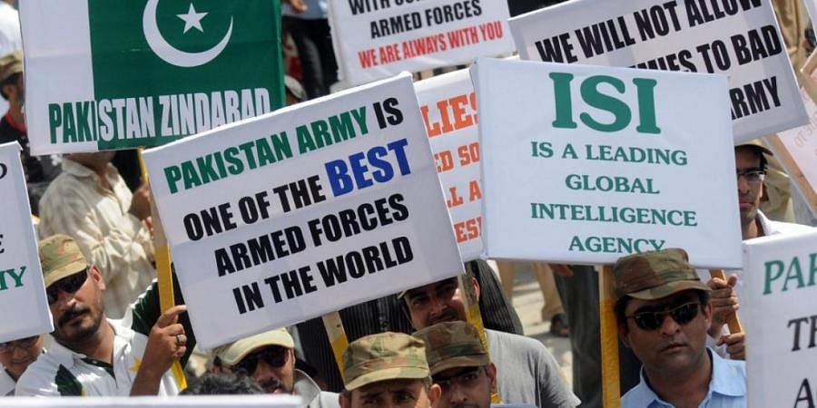 Pakistanis hold placards as they march during a rally in favour of Pakistan's army and Inter-Services Intelligence (ISI) in Karachi