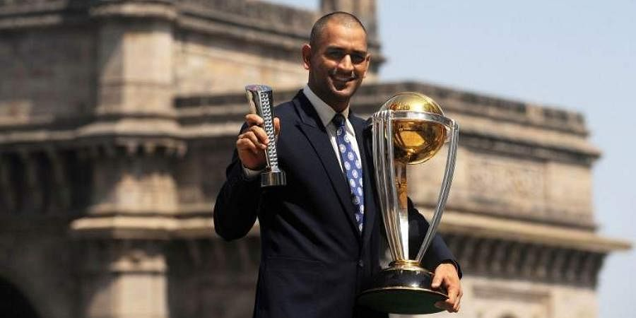 MS Dhoni poses with the Man of the Match and the ICC Cricket World Cup trophy.