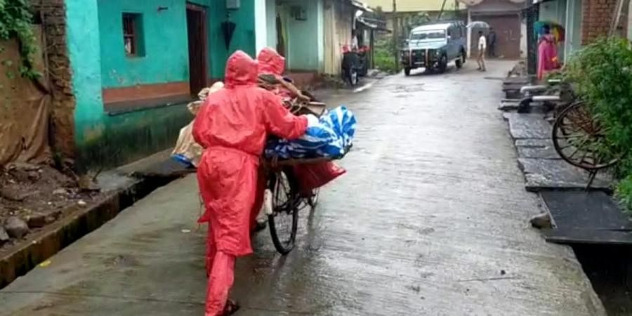 Family members carrying the dead body to crematorium using a bicycle