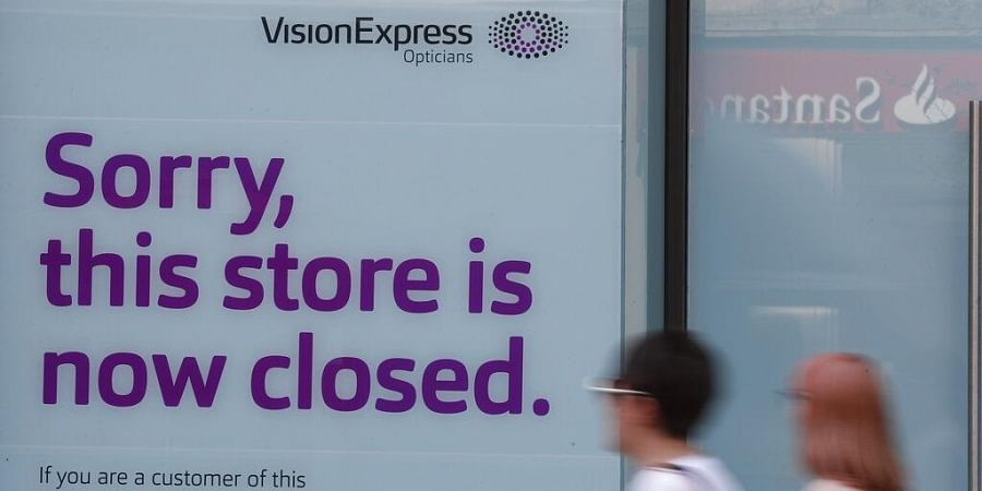 Pedestrians pass by a closed branch of Vision Express in Kensington, London, Wednesday, Aug. 12, 2020.