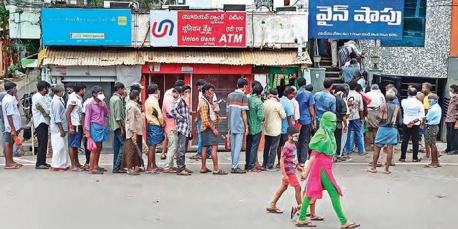 Public flout physical distancing norms as they queue up to buy liquor, in Vijayawada.