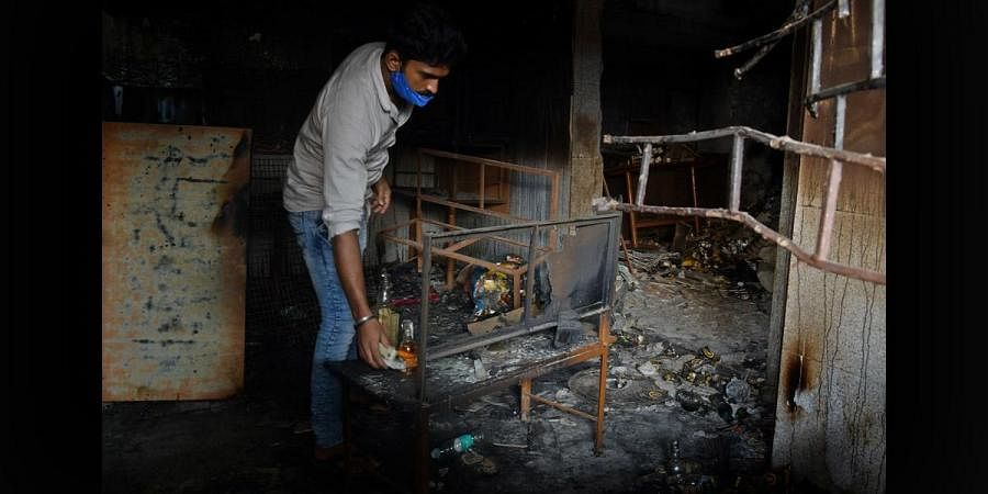 An owner of a liquor store inspects his shop after it was burnt down during the DJ Halli riots in Bengaluru