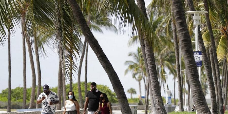 A group of people, wearing face masks to prevent the spread of the coronavirus, walk along a beach path on Miami Beach, Florida's famed South Beach (Photo | AP)