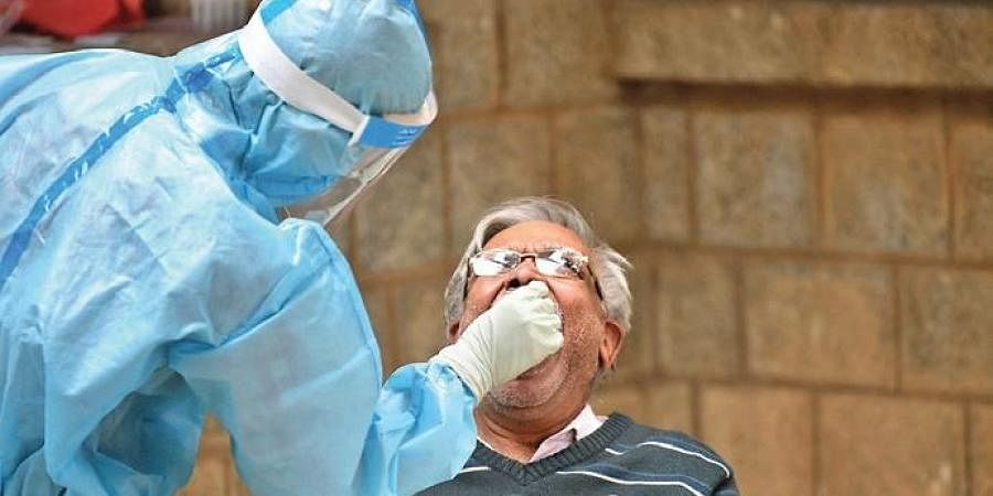 An elderly man gives his sample for COVID-19 testing at a clinic.
