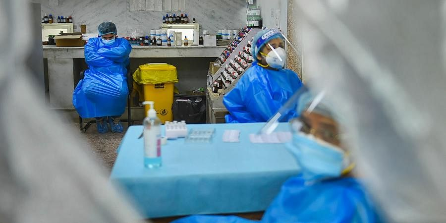 Health workers rest during at a COVID-19 testing centre. (Photo PTI)