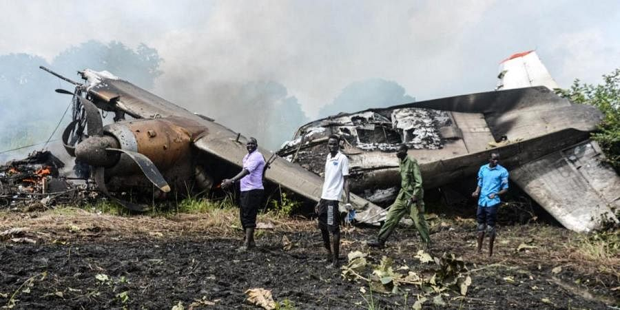 People stand near the cargo plane belonging to a local operator that crashed seven kilometres west of the Juba International airport