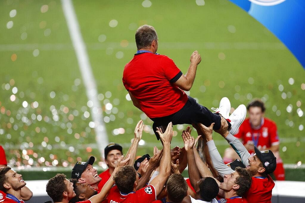 Munich player lift Bayern's head coach Hans-Dieter Flick as they celebrate the treble-winning moment. (Photo | AP)