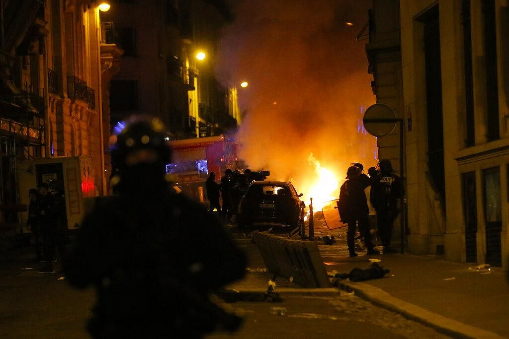 French police officers watch a car burning near the Champs-Elysee avenue following incidents after the Champions League final match in which PSG lost to Bayern Munich. (Photo | AP)