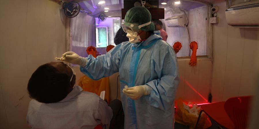 A health worker inside a mobile lab takes nasal swab sample for a COVID- 19 antigen test.