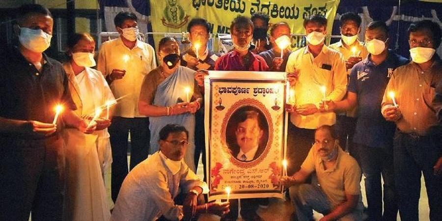 Doctors from Mysuru chapter of Indian Medical Association hold a candlelight vigil in memory of Dr Nagendra at DHO office in Mysuru on Sunday.