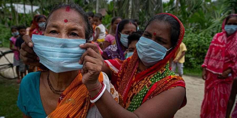 A woman helps another wear a mask as a precaution against the coronavirus.