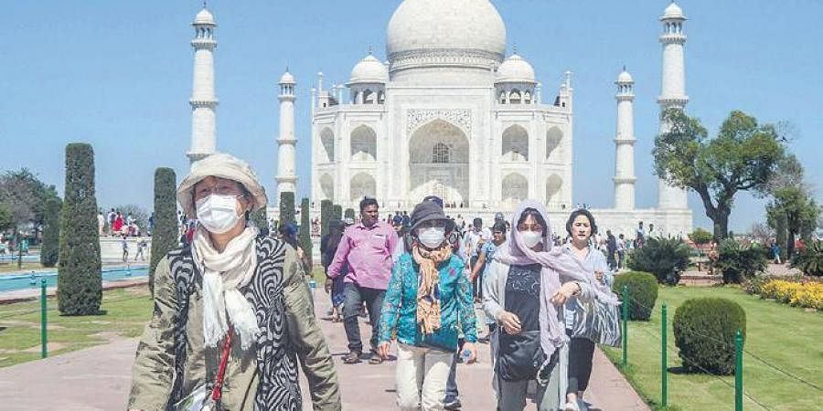 Tourists wearing protective masks at the Taj Mahal in Agra on Monday