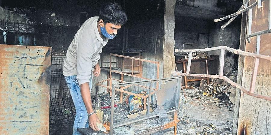 An owner of a liquor store inspects his shop after it was burnt down during the recent DJ Halli riots in Bengaluru.