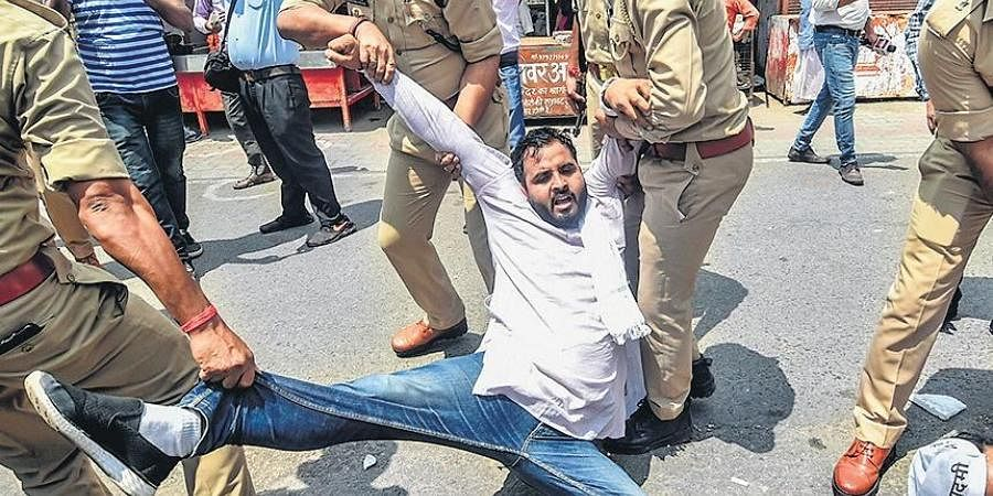 Aam Admi Party workers being detained by police during a protest demanding to postpone JEE/NEET exams in Lucknow on Friday.