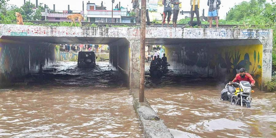 Commuters move through a waterlogged underpass after heavy rainfall in Bhopal Saturday Aug 29 2020.