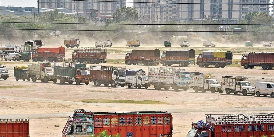 Trucks move slowly in a queue at Burari, during the ongoing nationwide COVID-19 lockdown, in New Delhi
