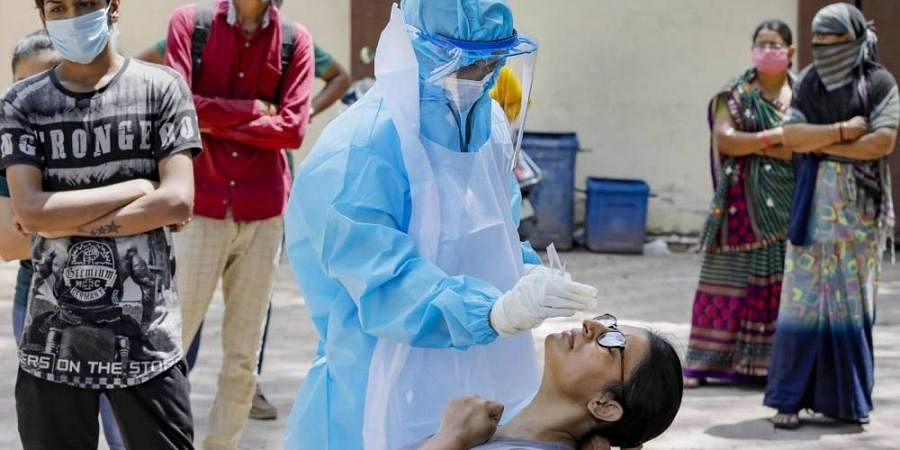 A healthcare worker wearing a PPE kit takes a sample of a woman for COVID-19 test at a residential area. (Photo   PTI)
