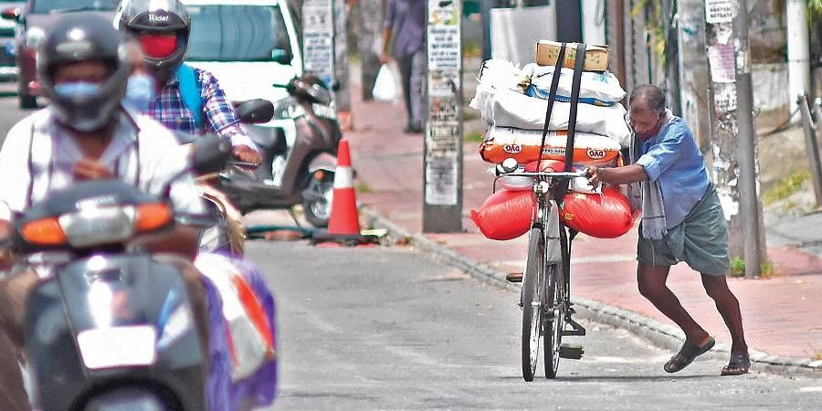 A man returns with provisions on his bicycle from Chalai wholesale market through the road near Ayurveda College in Thiruvananthapuram. Shops selling essential items at the wholesale market in Chalai