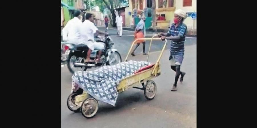 Man carrying the body of an elderly woman who succumbedto Covid, in Theni district.