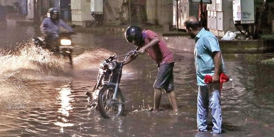 Commuters wade through a flooded road at Laxmisagar in Bhubaneswar on Sunday I Irfana