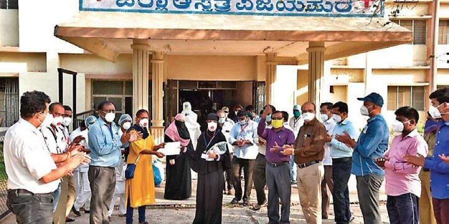 Hospital workers cheer as patients leave the hospital after successfully  recovering from Covid-19, in Vijayapura