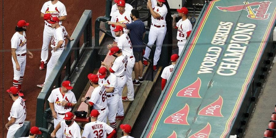 In this July 24, 2020, file photo, members of the St. Louis Cardinals wait to be introduced before the start of a baseball game against the Pittsburgh Pirates.