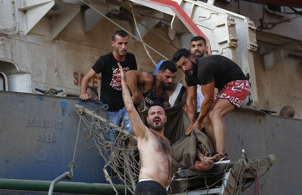 Civilians help to evacuate an injured sailor from a ship which was docked near the explosion scene that hit the seaport of Beirut, Lebanon, Tuesday.
