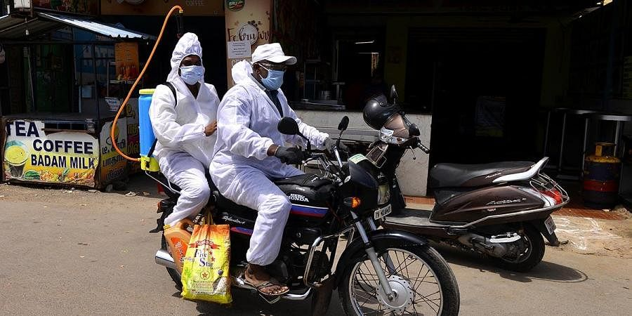 Sanitation workers leaving after spraying disinfectant at Arumbakkam in Chennai