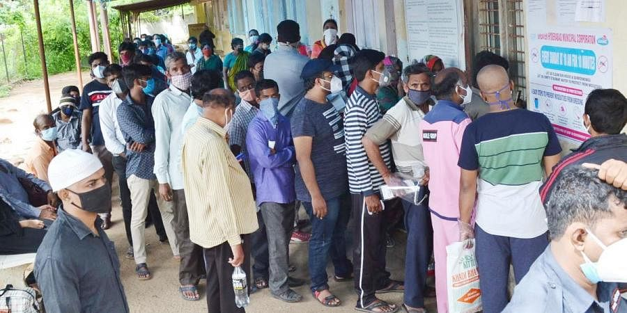 People stand in queue without social distance to get COVID-19 tests at a fever hospital in Hyderabad