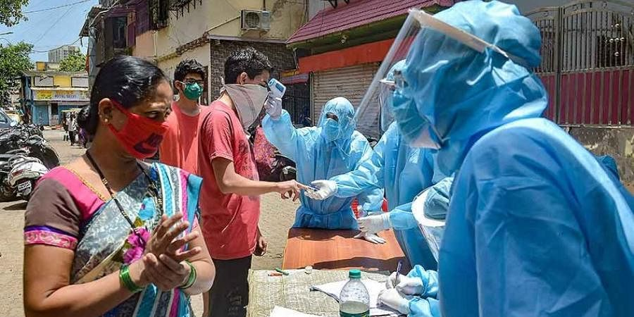 Volunteers carry out thermal tests of residents at Dharavi during ongoing COVID-19 lockdown, in Mumbai.