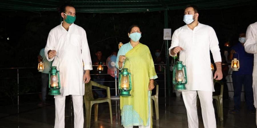 Ex- Bihar CM Rabri Devi along with her two sons - Tej Pratap (L)and Tejashwi (R) - burnt lanterns to protest against unemployment crisis