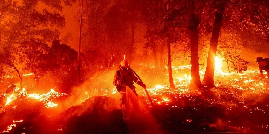 A firefighter battles the Creek Fire as it threatens homes in the Cascadel Woods neighborhood of Madera County, Calif., on Monday, Sept. 7, 2020. (Photo | AP)
