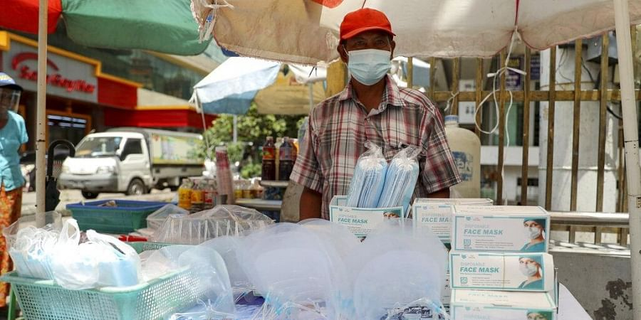 A vendor selling face masks and shields waits for customers at a roadside shop in Yangon, Myanmar, Thursday, Sept. 10, 2020. (Photo | AP)