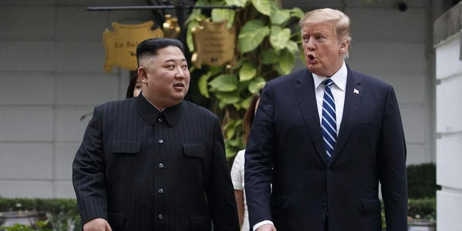 President Donald Trump and North Korean leader Kim Jong Un take a walk after their first meeting