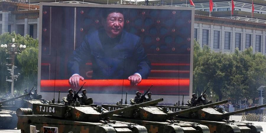 Chinese President Xi Jinping is displayed on a screen as Type 99A2 Chinese battle tanks take part in a parade. (Photo | AP)
