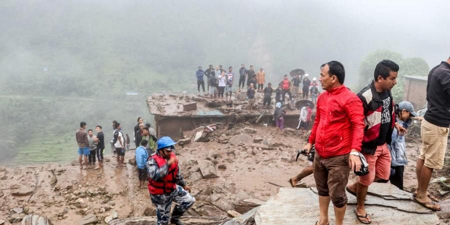 Rescue workers and residents gather for search at the scene of a landslide following heavy rains in Bahrabise municipality of Sindhupalchok district, some 90 kms northeast of Kathmandu. (Photo | AFP)