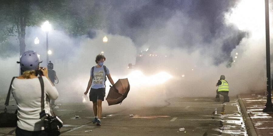 National Guard troops fire tear gas on the crowd to disperse them after a warning was ignored during protests, Monday, Aug. 24, 2020, in Kenosha.