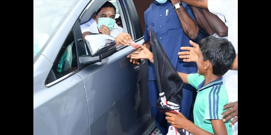 Chief Minister Edappadi K Palaniswami giving a chocolate to a boy who was waiting to greet him on his arrival at Kancheepuram
