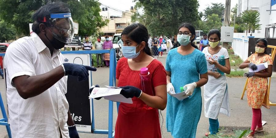 Security personnel checking the documents of a medical aspirant outside a NEET Examination centre in Coimbatore