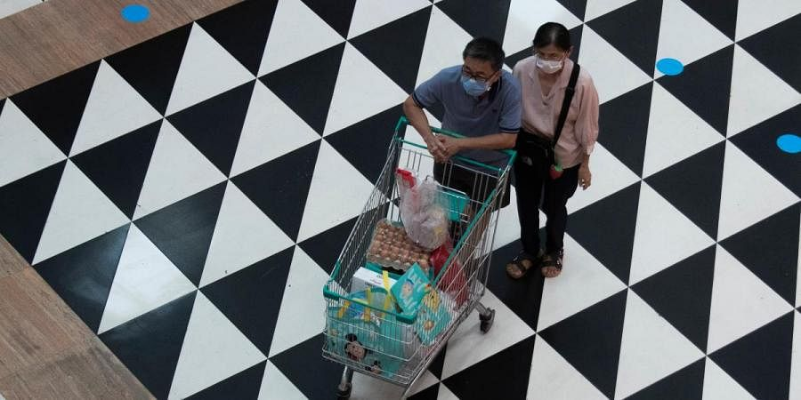 Shoppers wearing face masks to help curb the spread of the coronavirus push their shopping cart at shopping mall in Bangkok, Thailand, Friday, June 12, 2020.