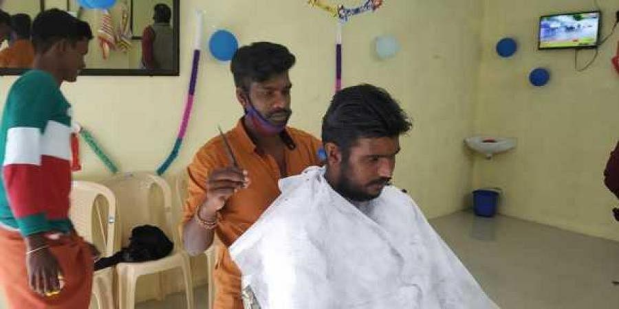 A man gets his hair cut at the public barber shop at Vattavada
