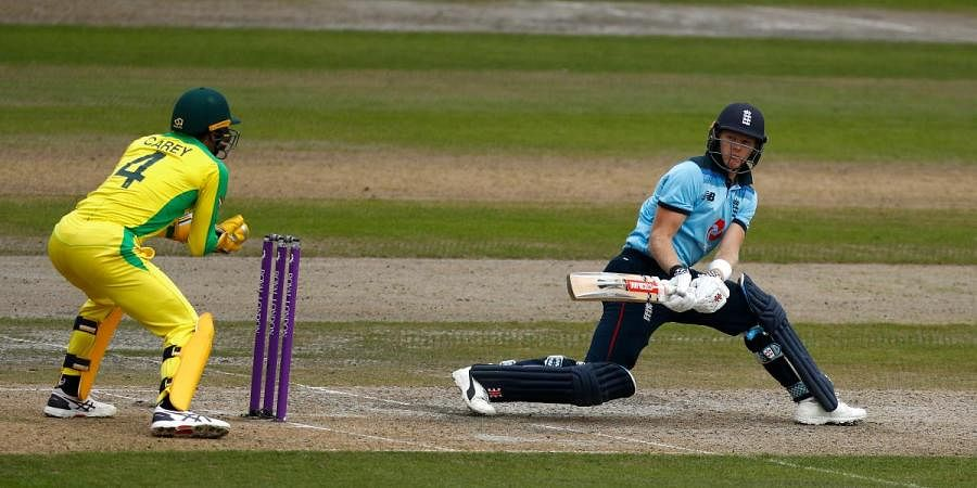 England's Sam Billings (R) plays a reverse sweep during the third ODI against Australia, at Old Trafford in Manchester
