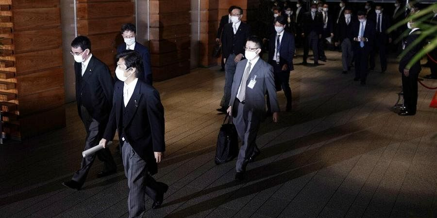 Newly appointed ministers, left, leave the official residence for the Imperial Palace to attend the attestation ceremony of the new cabinet by Prime Minister-elect Yoshihide Suga.