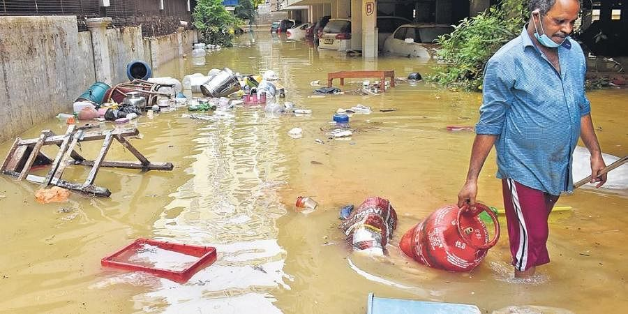 A man picking up items that floated away in the floods triggered by a Manjeera pipeline burst, at an apartment complex in Madinaguda on Tuesday